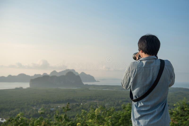 Homem asiático novo que toma a foto do cenário bonito imagens de stock royalty free