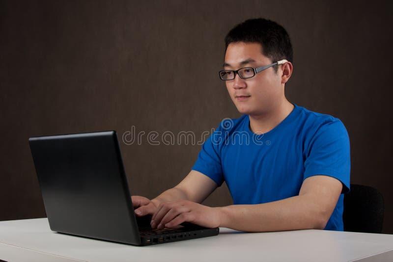 Homem asiático novo que trabalha em seu computador portátil foto de stock