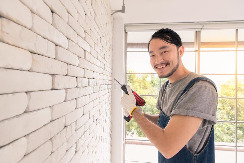 Homem asiático novo que usa a broca elétrica na parede de tijolo branca na sala imagem de stock
