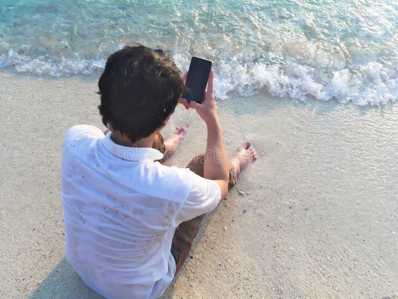 Homem asiático novo que usa o telefone esperto móvel no Sandy Beach Conceito das férias de verão imagens de stock royalty free