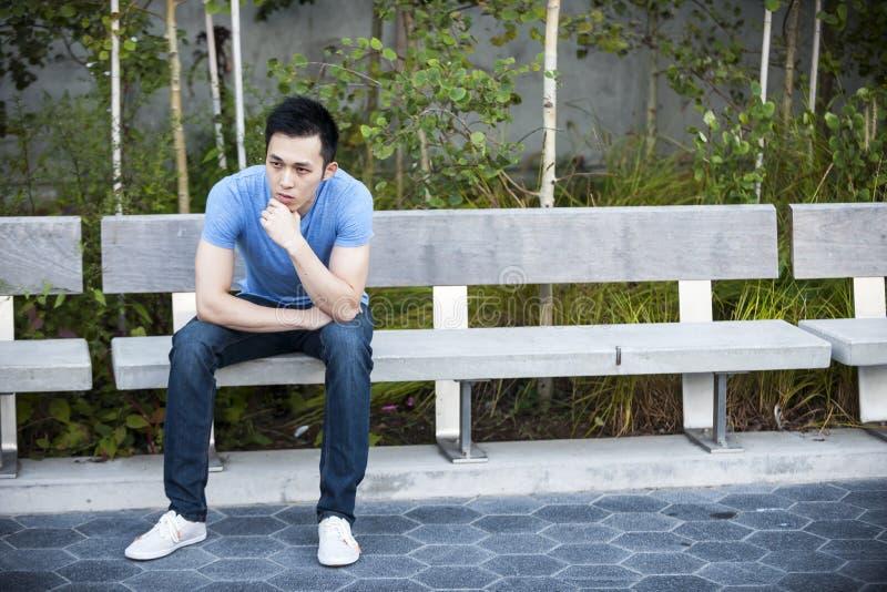 Homem asiático novo sério no banco imagens de stock royalty free