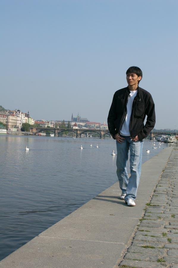 Homem asiático que anda ao longo da terraplenagem fotos de stock royalty free