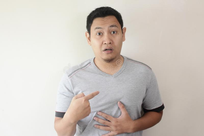 Homem asiático que aponta-se com expressão infeliz fotos de stock