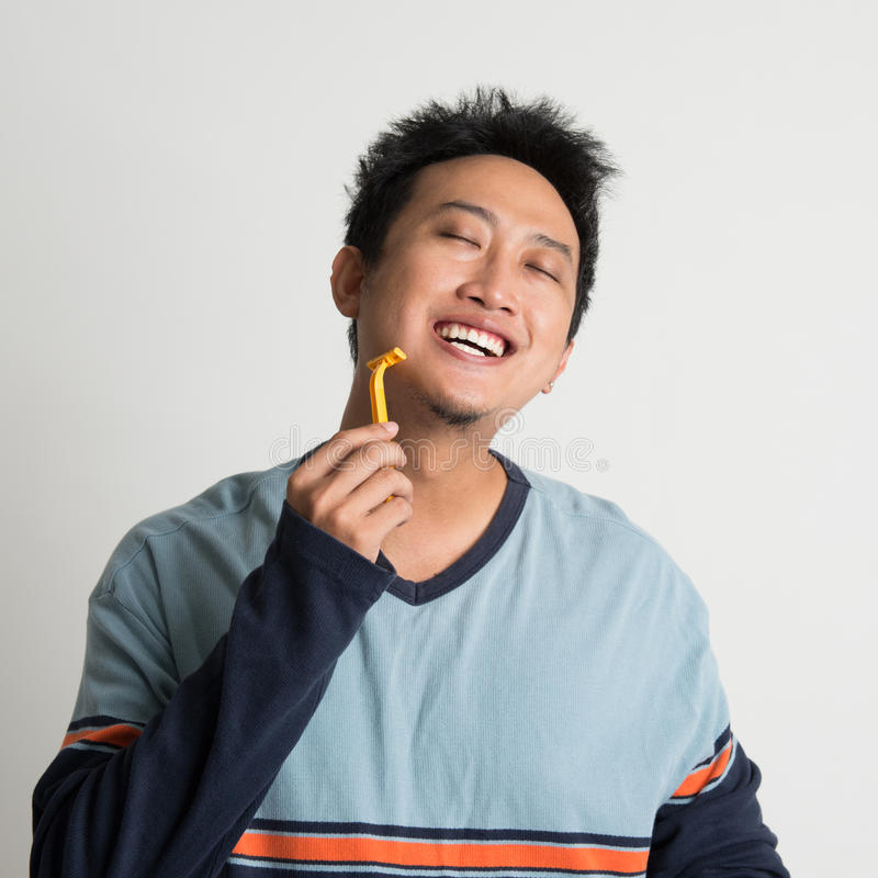 Homem asiático que barbeia sua barba imagens de stock