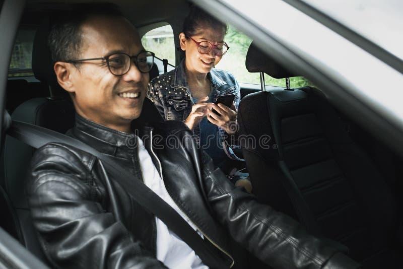 Homem asiático que conduz o automóvel de passageiros e a mulher com sorriso toothy esperto do telefone à disposição com cara da f foto de stock royalty free