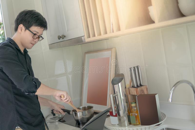 Homem asiático que cozinha com potenciômetro e concha na cozinha imagens de stock royalty free