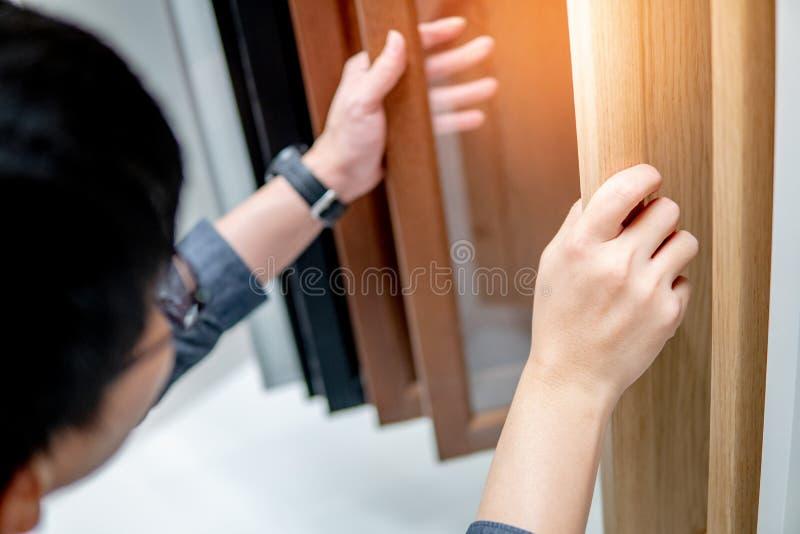 Homem asiático que escolhe materiais do armário ou da bancada foto de stock royalty free