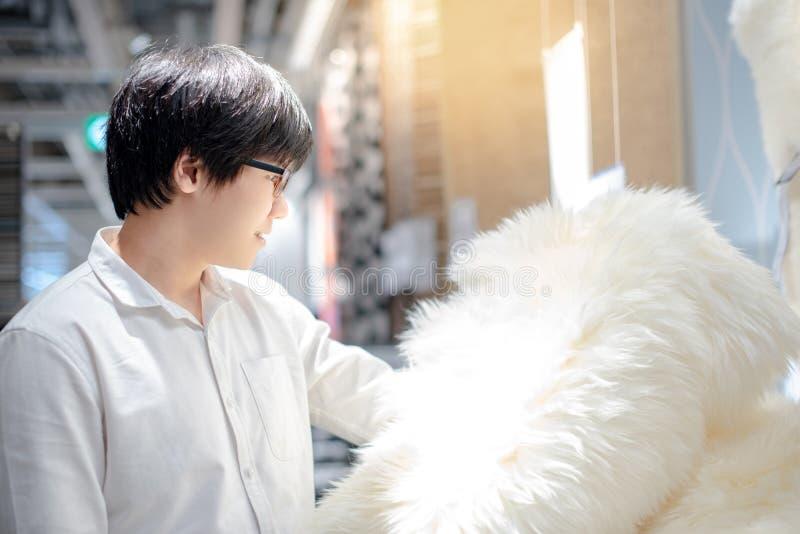 Homem asiático que escolhe o tapete da pele na loja fotografia de stock royalty free