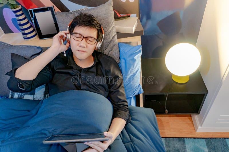 Homem asiático que escuta a música usando a tabuleta na cama fotografia de stock