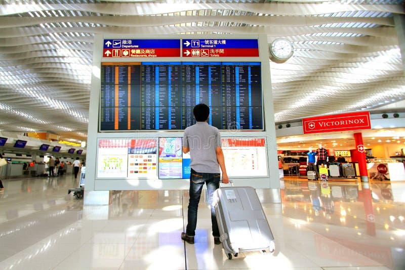 Homem asiático que está e que guarda a bagagem e que verifica o voo na placa do tempo de partida no aeroporto internacional de Ho fotos de stock royalty free