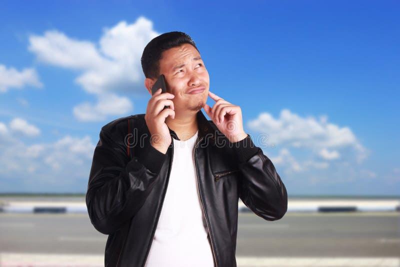Homem asiático que fala no telefone, gesto de pensamento fotos de stock