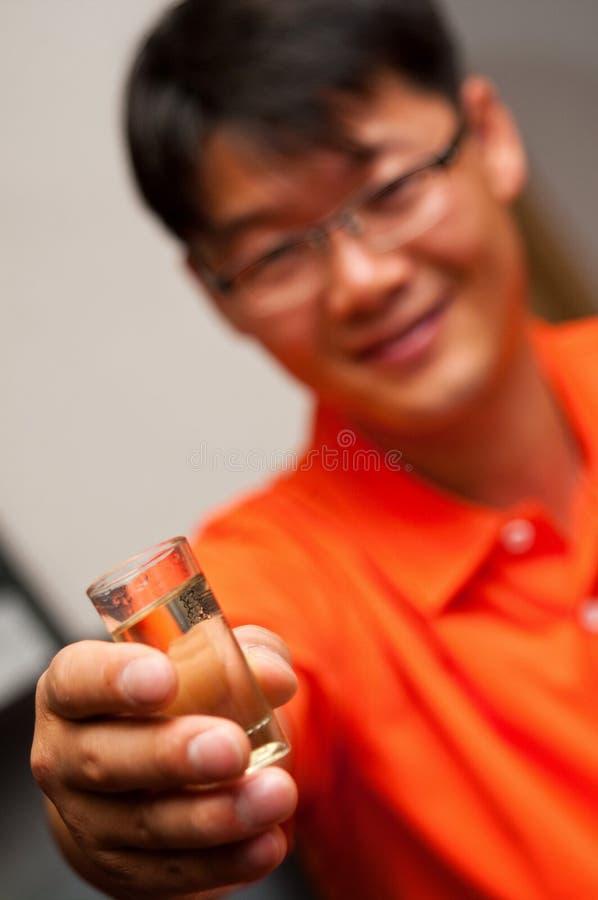 Homem asiático que guarda o vidro da vodca fotos de stock