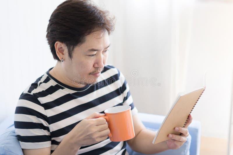 Homem asiático que guarda uma caneca e que lê um livro foto de stock royalty free