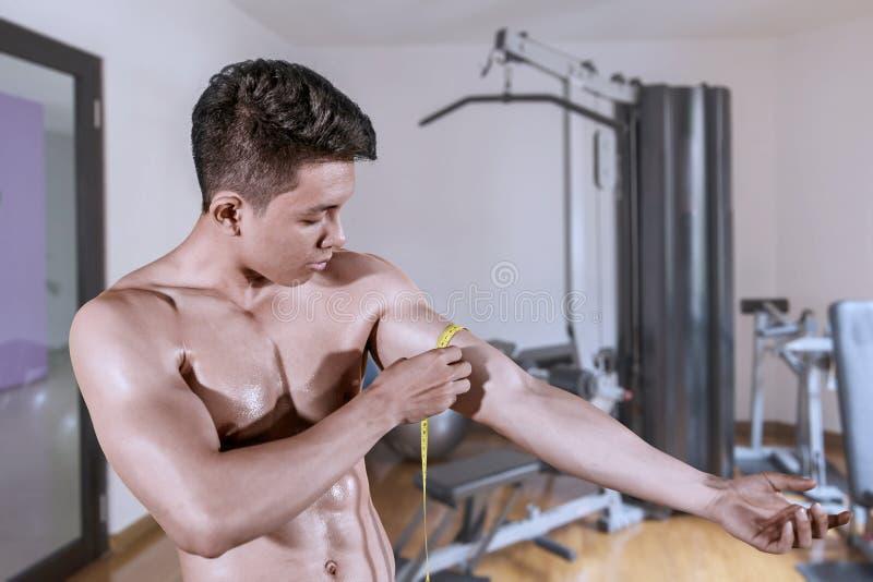 Homem asiático que mede seu bíceps muscular imagem de stock royalty free