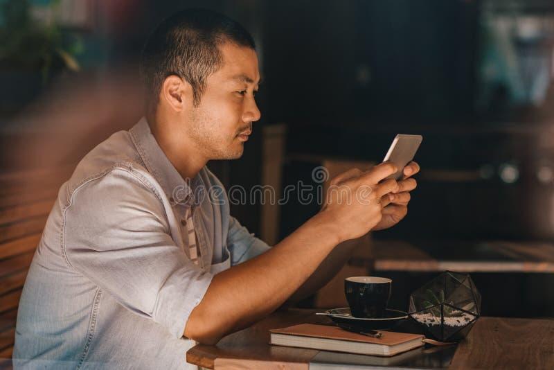 Homem asiático que senta-se em um café usando a tabuleta digital imagem de stock royalty free