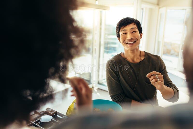 Homem asiático que senta-se na casa de praia com amigos fotos de stock royalty free