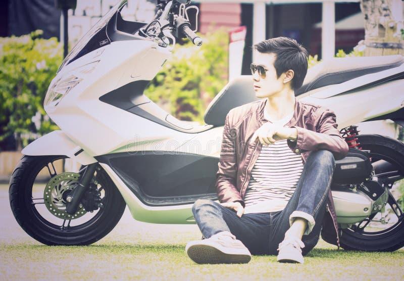 Homem asiático que senta-se na terra com seu 'trotinette' exterior imagem de stock