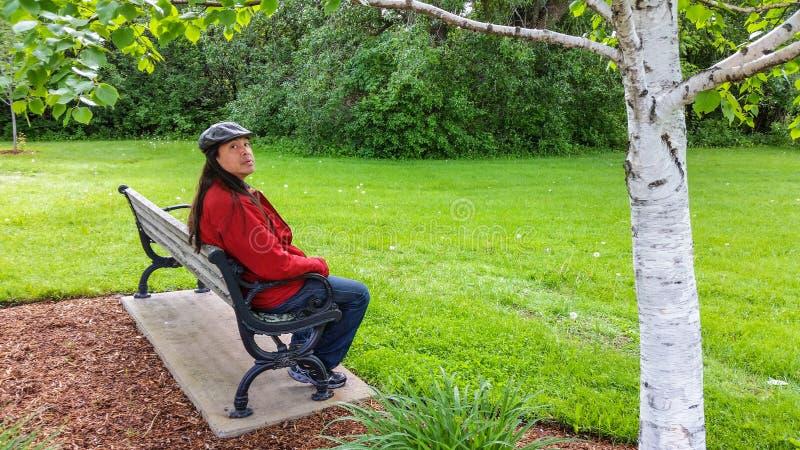 Homem asiático que senta-se no banco que olha para trás fotografia de stock