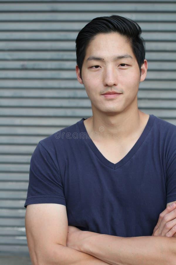 Homem asiático que sorri com seus braços cruzados fotografia de stock royalty free