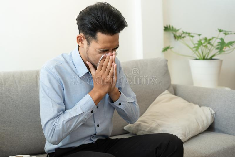 Homem asiático que tem gripe e espirra usando tecidos de papel sentados em sofá em casa, conceitos de saúde e doenças imagem de stock