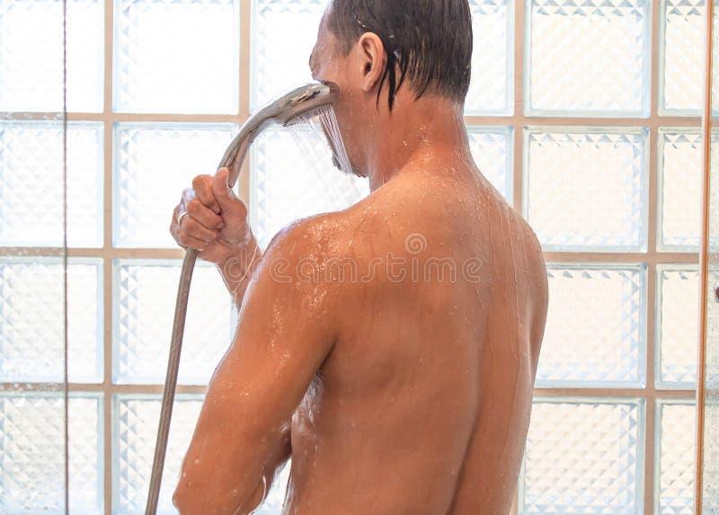 Homem asiático que toma um chuveiro no banheiro fotografia de stock