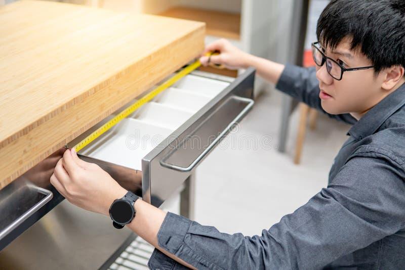Homem asiático que usa a fita métrica na gaveta foto de stock