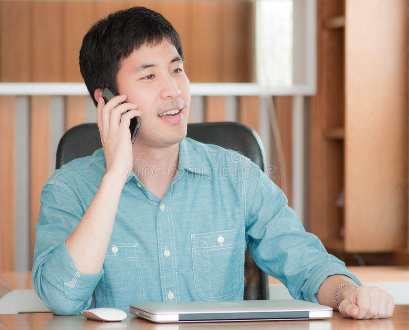 Homem asiático que usa o telefone celular foto de stock royalty free
