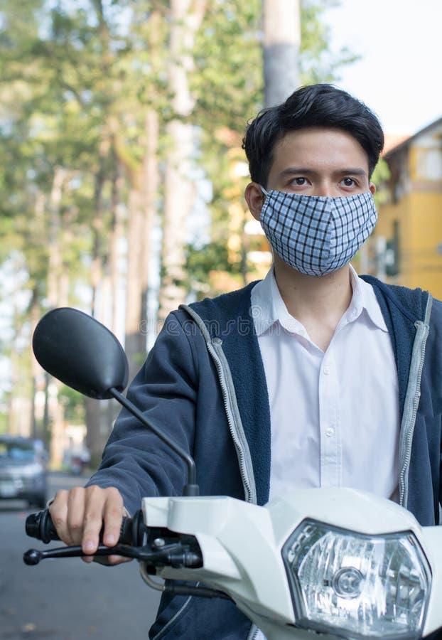 Homem asiático que veste uma máscara para diminuir a poluição do tráfego fotografia de stock