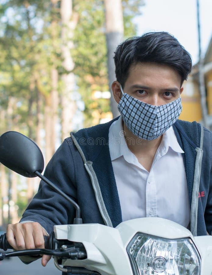 Homem asiático que veste uma máscara para diminuir a poluição do tráfego imagens de stock