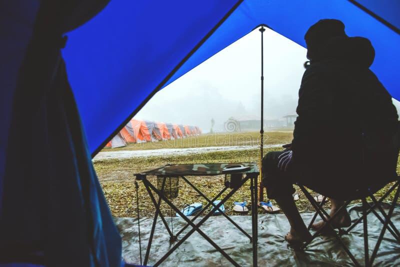 Homem asiático relaxa no feriado acampamento na Montanha sente-se relaxado na cadeira Na atmosfera a chuva cai e a neblina cai imagens de stock