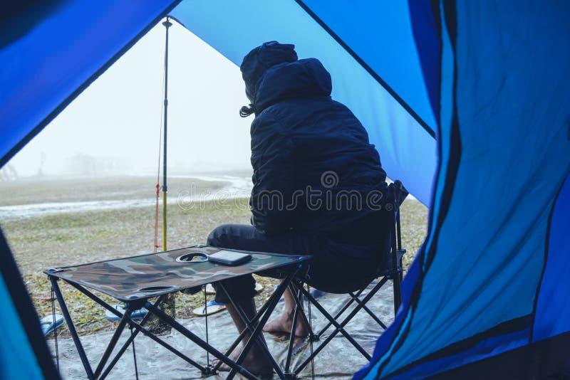 Homem asiático relaxa no feriado acampamento na Montanha sente-se relaxado na cadeira Na atmosfera a chuva cai e a neblina cai imagem de stock royalty free