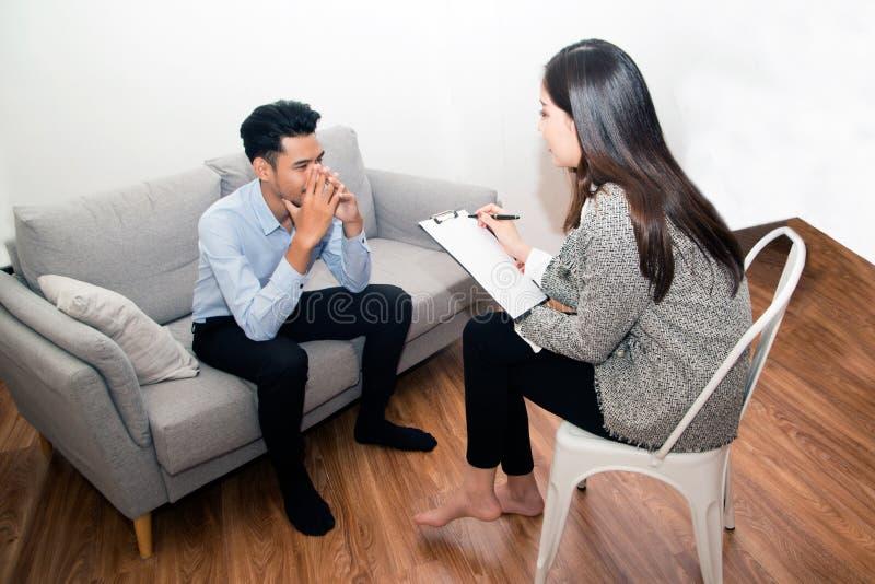 Homem asiático sentado no sofá com psicólogo fotografia de stock