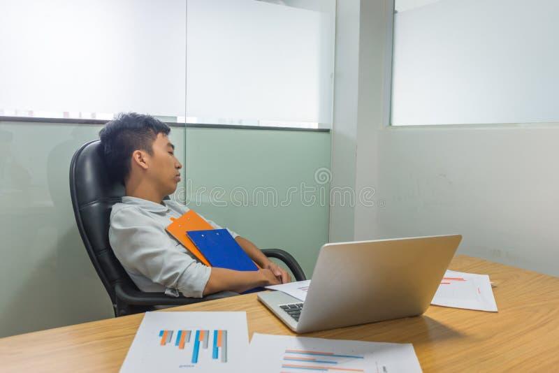 Homem asiático sobrecarregado adormecido caído com documentos em suas mãos fotografia de stock