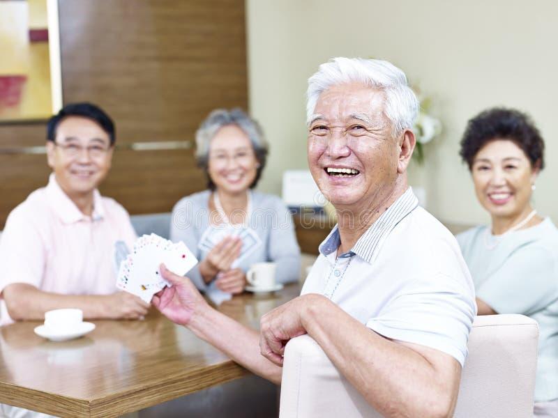 Homem asiático superior em cartões de jogo com amigos imagem de stock