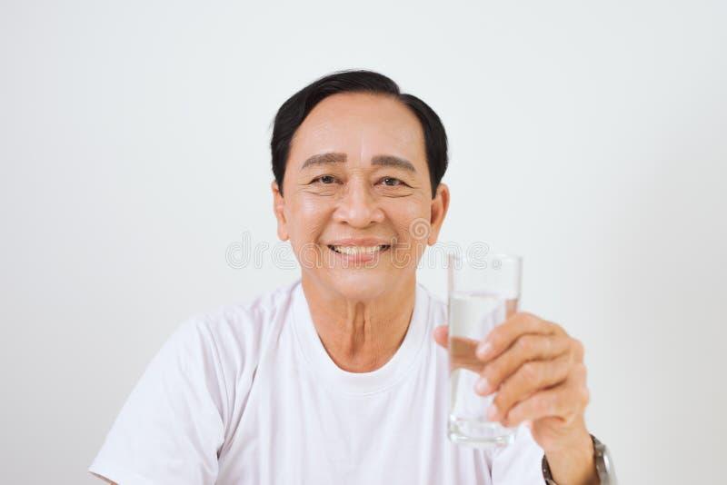 Homem asiático superior que guarda um vidro da água pura imagens de stock