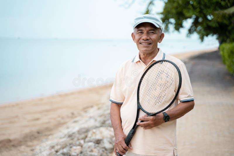 Homem asiático superior que sorri com tênis da raquete fotos de stock
