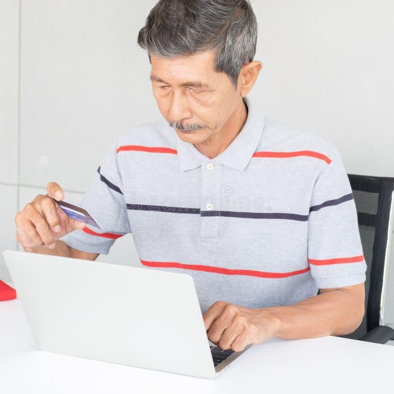 Homem asiático superior que usa em linha um cartão de crédito, conceito em linha de compra fotografia de stock royalty free