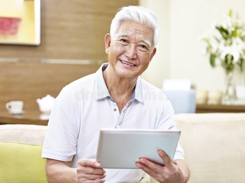 Homem asiático superior que usa o tablet pc foto de stock royalty free