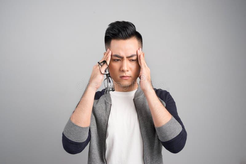 Homem asiático thoughful triste novo que tem a dor de cabeça após o trabalho imagem de stock