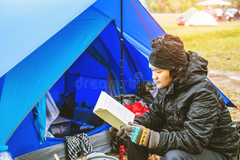Homem asiático viaja relaxando acampar no feriado acampamento na Montanha sente-se relaxe leia um livro na cadeira Tailândia fotos de stock royalty free