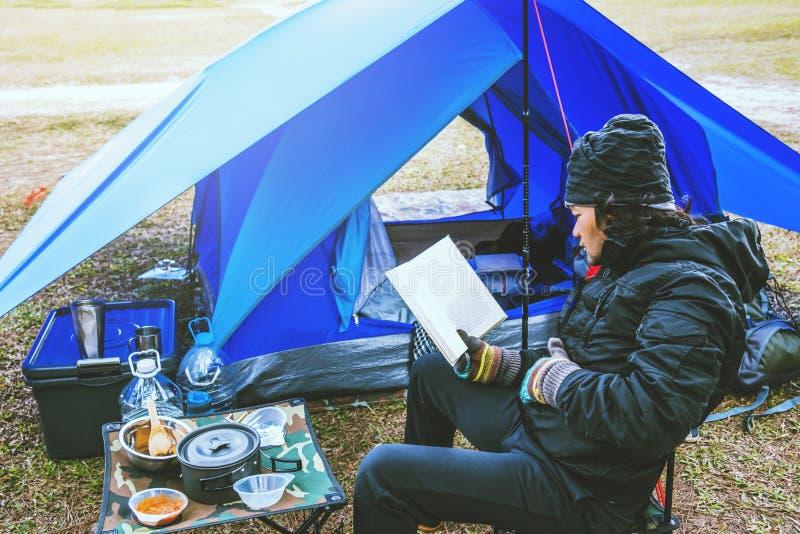 Homem asiático viaja relaxando acampar no feriado acampamento na Montanha sente-se relaxe leia um livro na cadeira Tailândia imagem de stock royalty free