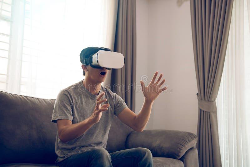 Homem asi?tico novo que veste vidros da realidade virtual na sala de visitas para admirar a realidade virtual imagem de stock royalty free