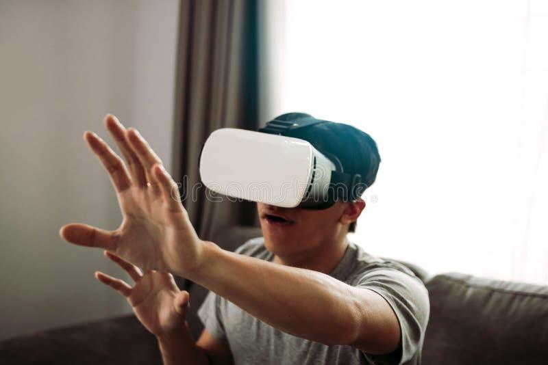 Homem asi?tico novo que veste vidros da realidade virtual na sala de visitas para admirar a realidade virtual imagem de stock