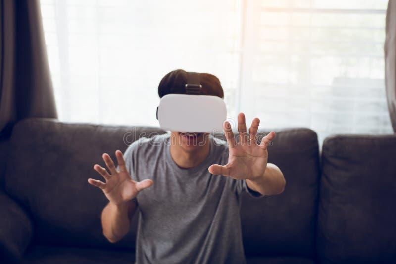 Homem asi?tico novo que veste vidros da realidade virtual na sala de visitas para admirar a realidade virtual fotografia de stock