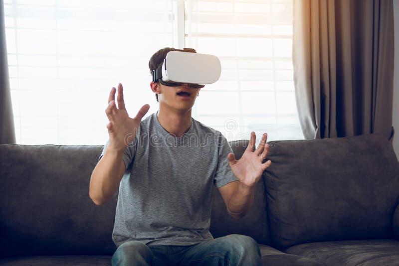 Homem asi?tico novo que veste vidros da realidade virtual na sala de visitas para admirar a realidade virtual fotos de stock