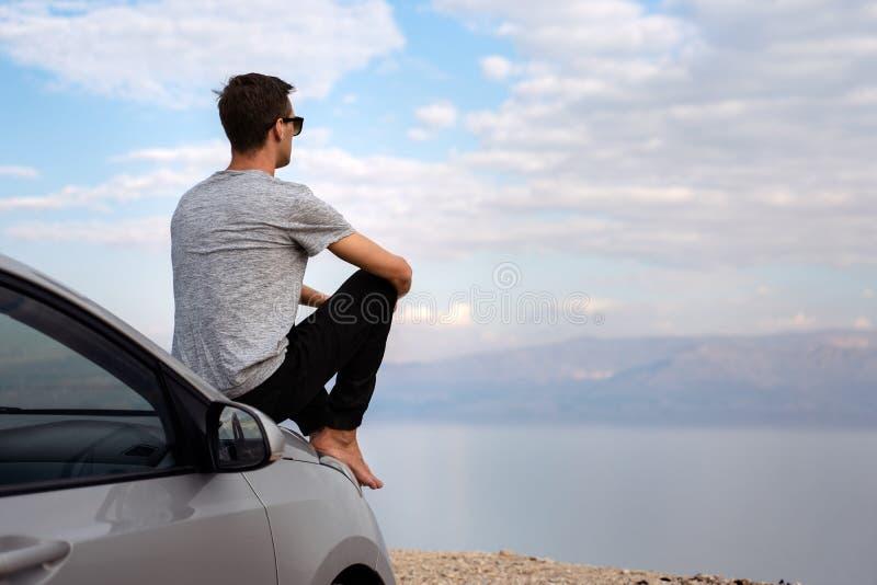 Homem assentado na capa do motor de um carro alugado em uma viagem por estrada em Israel imagem de stock royalty free