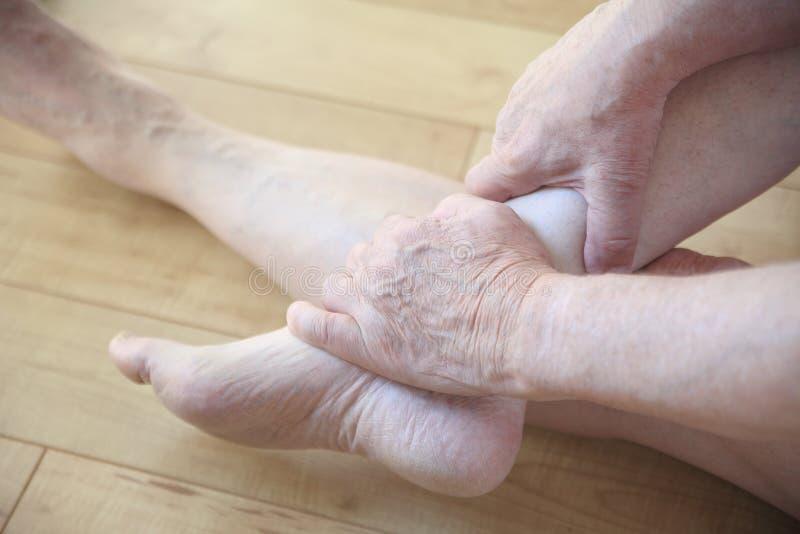 Homem assentado que guarda seu tornozelo doloroso imagem de stock royalty free