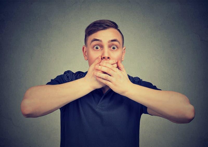 Homem assustado com as mãos que cobrem a boca que olha ansiosamente a câmera fotos de stock