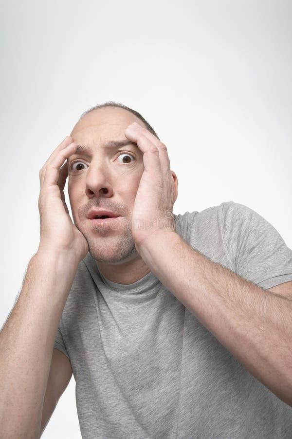Homem assustado com as mãos que cobrem a cara imagens de stock