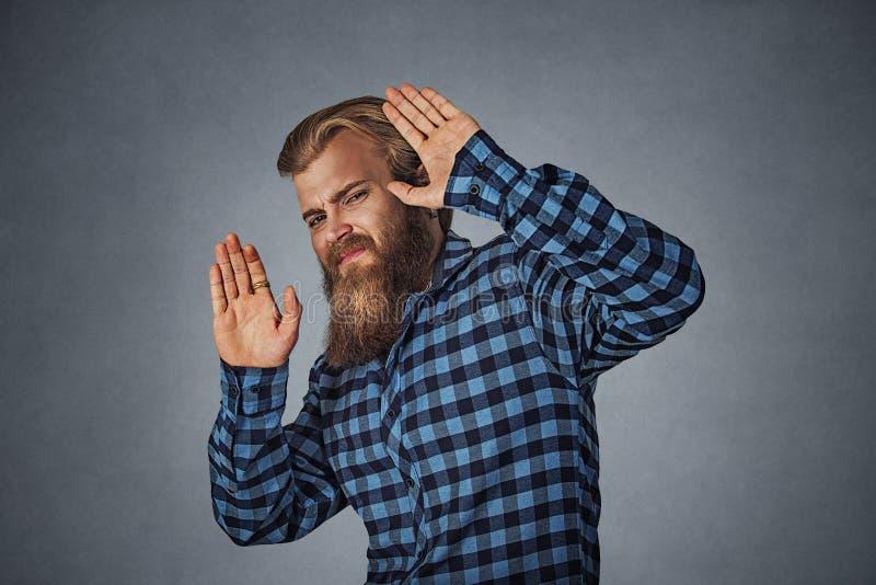 Homem assustado com a expressão chocada da cara que tenta proteger-se imagem de stock royalty free